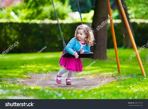 la swing little girl on a playground child playing outdoors in