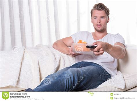 the man on the couch portrait young man sitting on couch and eating chips and