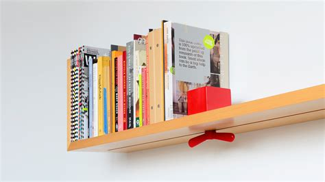 wall mounted shelf prevents toppling books with sliding