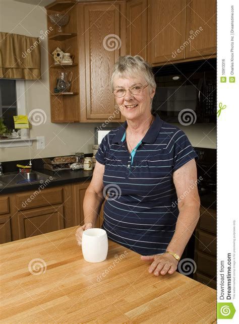 Standing In The Kitchen by Elderly Standing In Kitchen Royalty Free Stock Image