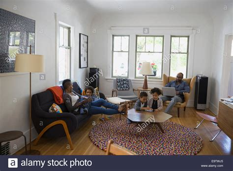 family in living room family relaxing and using technology in living room stock