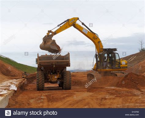 tracked backhoe digger loading large volvo dump truck site tipper stock photo  alamy