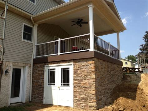gutterless roofs home design forum roof over deck deck with roof over and stone veneer traditional deck