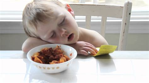 boy sleeping at dinner table after day of school