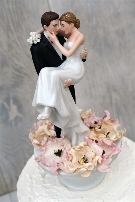 bride and groom wedding bed of roses groom holding the bride wedding cake topper