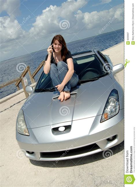 teen sitting  car hood  cell phone royalty  stock
