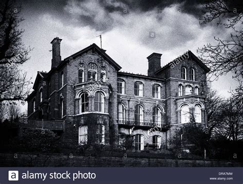 a moody grainy black and white image of a haunted house on
