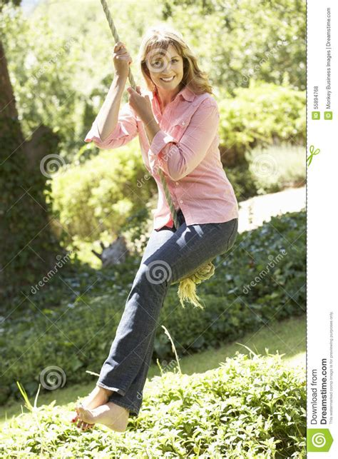 swing woman middle aged woman having fun on rope swing stock image