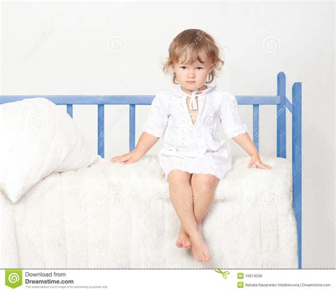 girl sitting on bed little girl sitting on the bed royalty free stock images