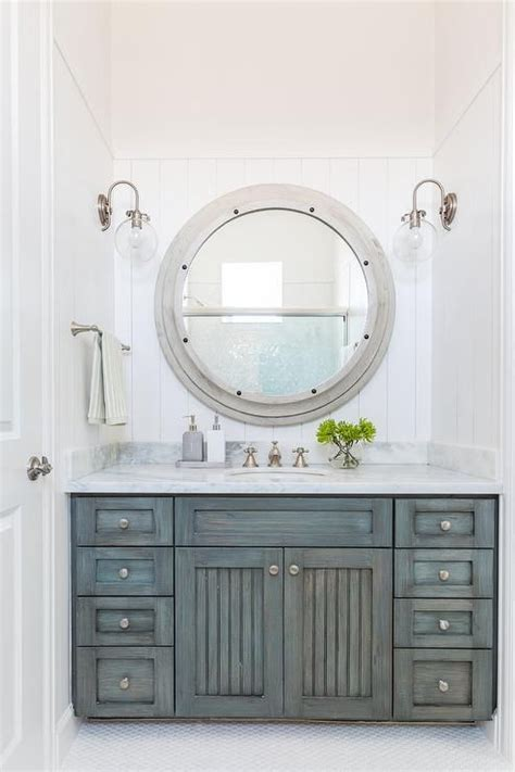 Faded teal vanity cabinets and round silver mirror for a