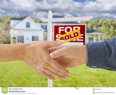 house shaking shaking hands in front of new house and sold sign stock photo image 56501059