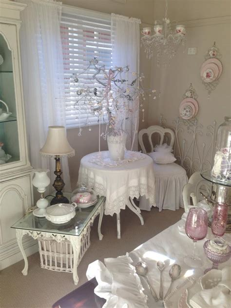 shabby chic room with sheers and blinds combo dishes displayed on wall and tea cup chandelier