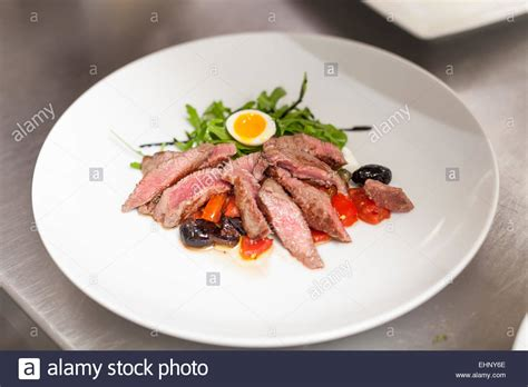 gravy boat restaurant littlehton menu chef plating up food in a restaurant pouring a gravy or