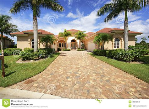 Cape Cod Home Designs florida luxury home with paver block driveway stock photo