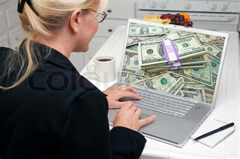 How To Win Money Easily - woman in kitchen using laptop to earn or win money screen can be easily used for your