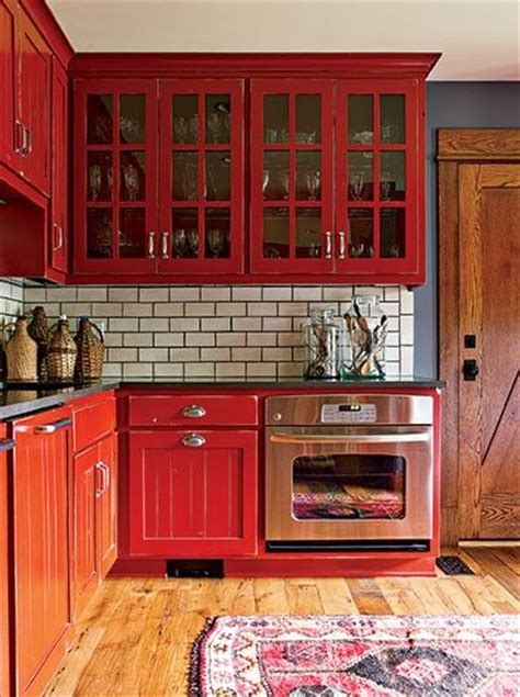 rustic red kitchen cabinets in lynne and jon beaver s colorful laundry room cum office