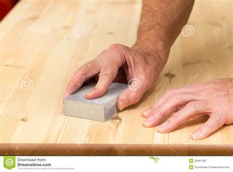 sanding detailed woodwork mans on sanding block on pine wood stock photos