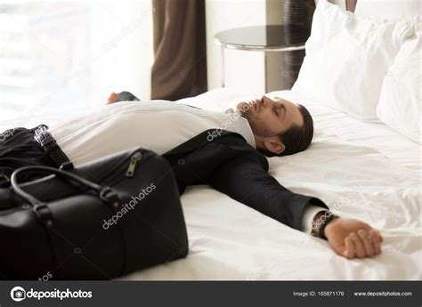lay on the bed exhausted businessman laying on bed in hotel room stock