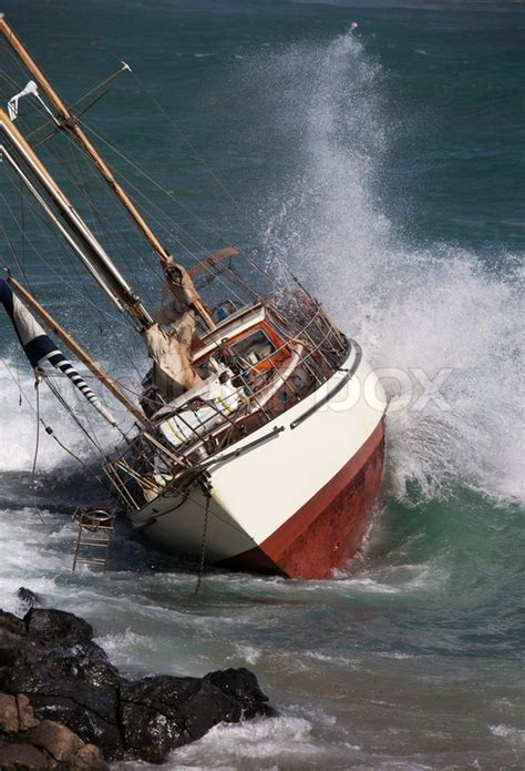 crash boat weather yacht crash on the rocks after stormy weather stock