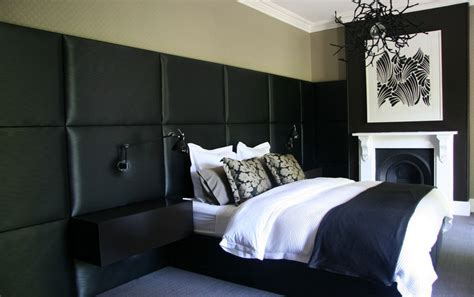 black leather headboard white bedding and chandelier
