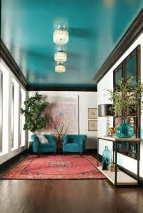 white walls are accented with striking black molding and a glossy turquoise ceiling coulter