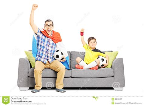 couch sport two male sport fans seated on a sofa watching sport stock
