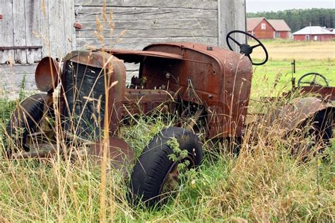 abandoned car in front of my house old broken rusty tractor abandoned in high grass in front of grey barn in the