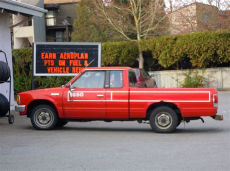 old nissan truck models old red nissan pickup truck at gas station free images