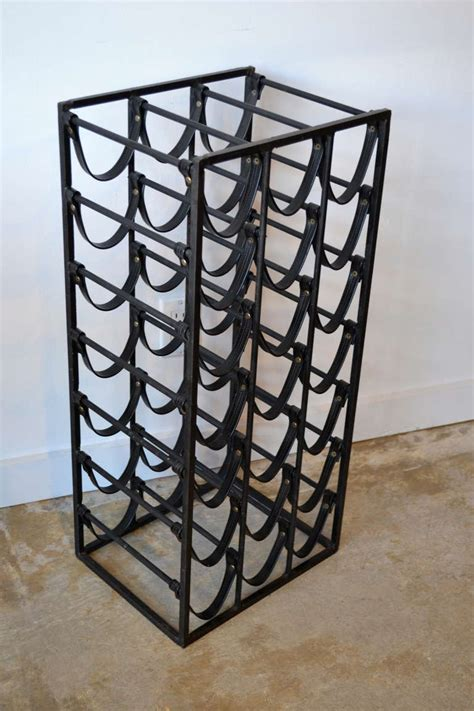 mid century wrought iron and leather wine rack in the