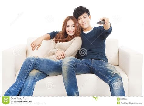 couple on sofa couple on sofa watching tv with remote control stock image