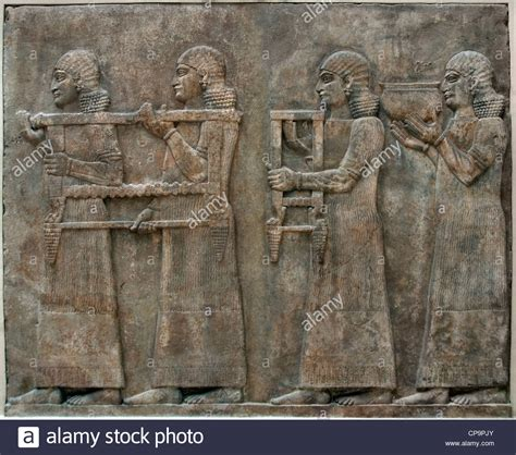 two servants carrying a chair and a vase neo assyrian