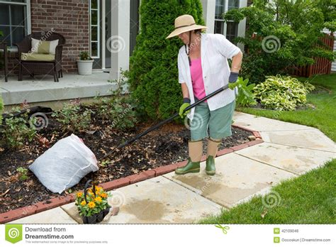 older lady doing cleaning work in the yard stock photo