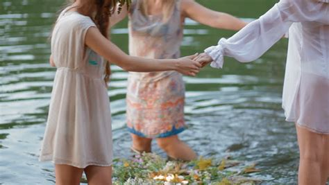hd stock video footage two women flaunt tradition and women dance in the circle around the wreath on the water