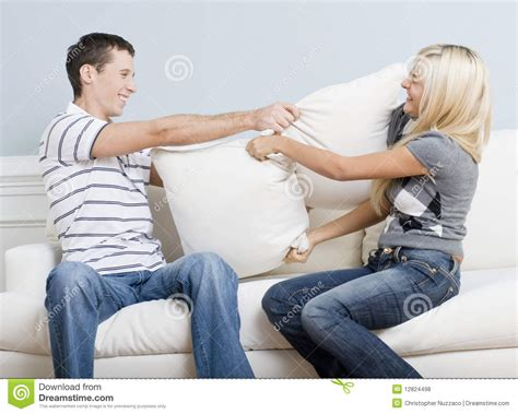 having on sofa young couple having a pillow fight on sofa royalty free