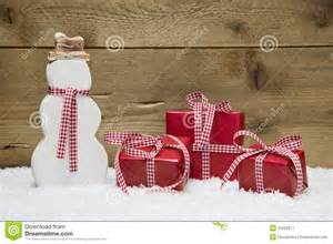 three red christmas presents and snowman with snow stock