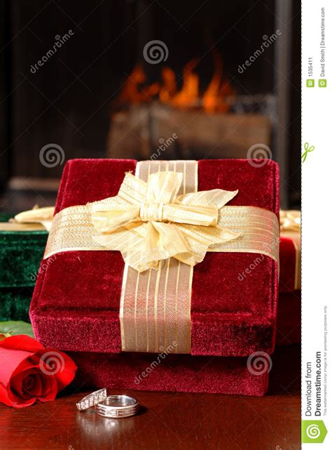 wedding rings with christmas gifts and a rose in front of
