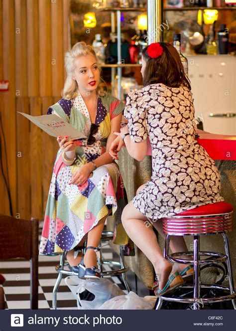 two in vintage dresses at a festival bar while