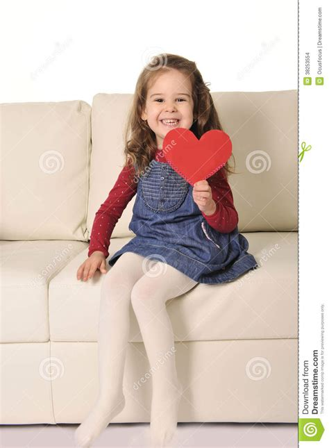 girl sitting on couch little girl sitting on couch holding red heart shape
