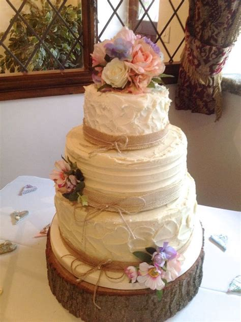 Rustic wedding cake with silk flower cake topper and two