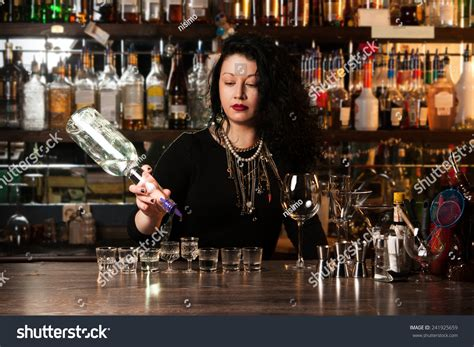 bartender photography bartender pouring alcohol into shot glasses stock photo