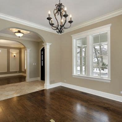 wood floors and white baseboards window trim