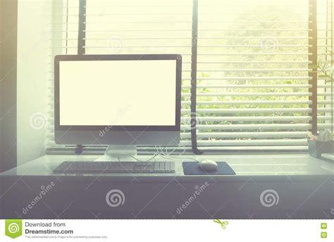 computer on white desk beside window stock photo image
