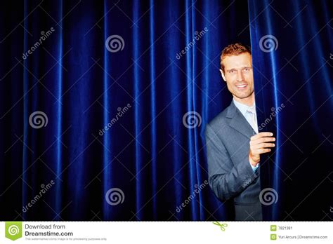 behind the blue curtain stock image business man peeping from behind blue curtain