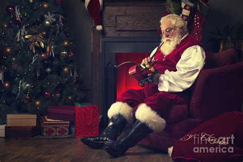 santa claus sitting at home working on painting a toy tra