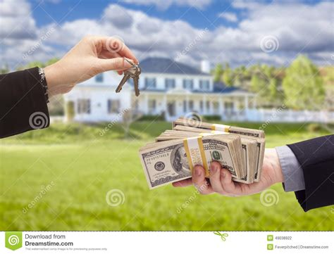 buy a house for free handing over cash for house keys in front of home stock photo image 49038922