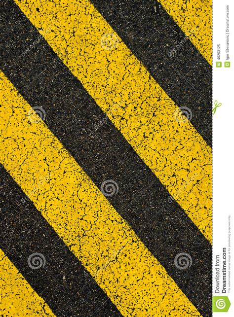 pattern of yellow lines on the roadway yellow striped road markings on black asphalt stock photo