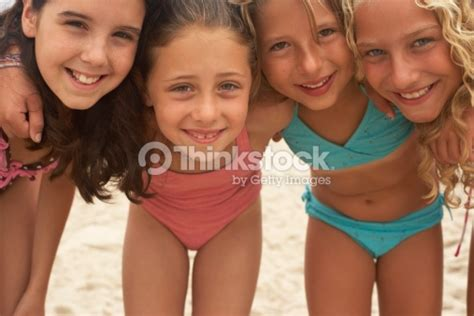 porsha laid out on beach in biki body four girls huddling together on beach smiling portrait