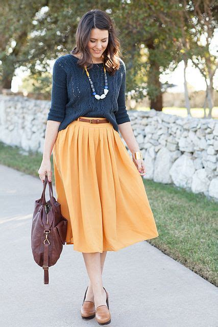 picture of yellow pleated midi skirt a grey sweater