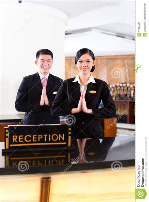 welcoming guests chinese asian reception team at hotel front desk stock image image 37384865