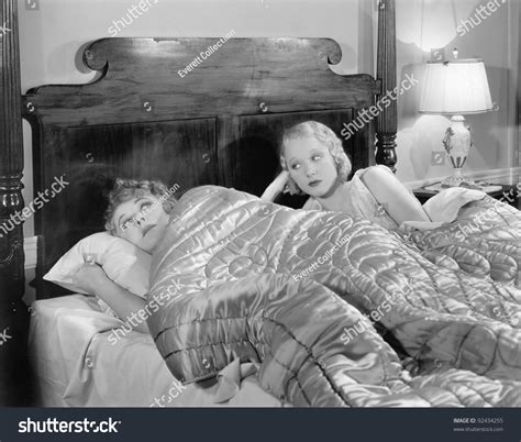 two women in bed two women together in bed under a blanket stock photo